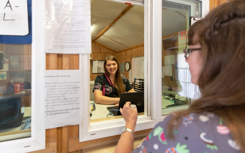 A smiling nurse hands a patient medication through a sliding dispensary window at Cove Forge Behavioral Health