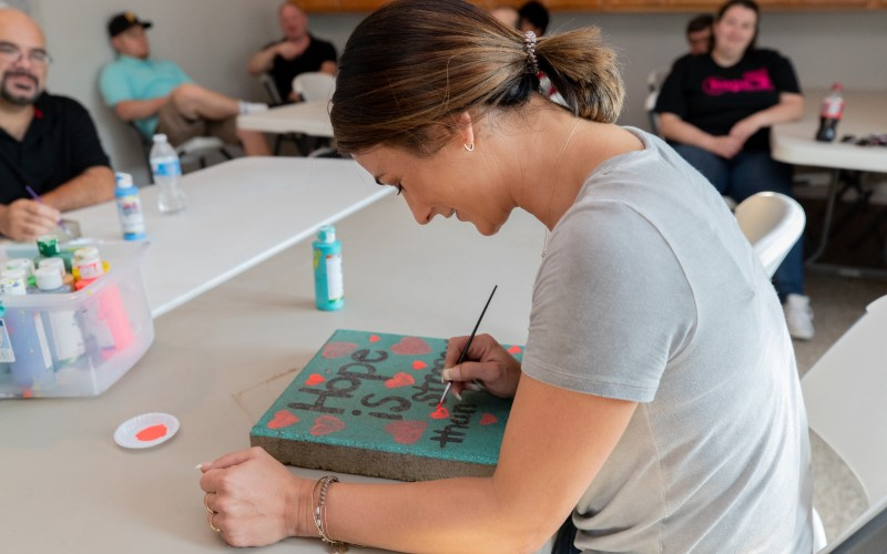 A patient works on an art project at Cove Forge Behavioral Health. The painting says