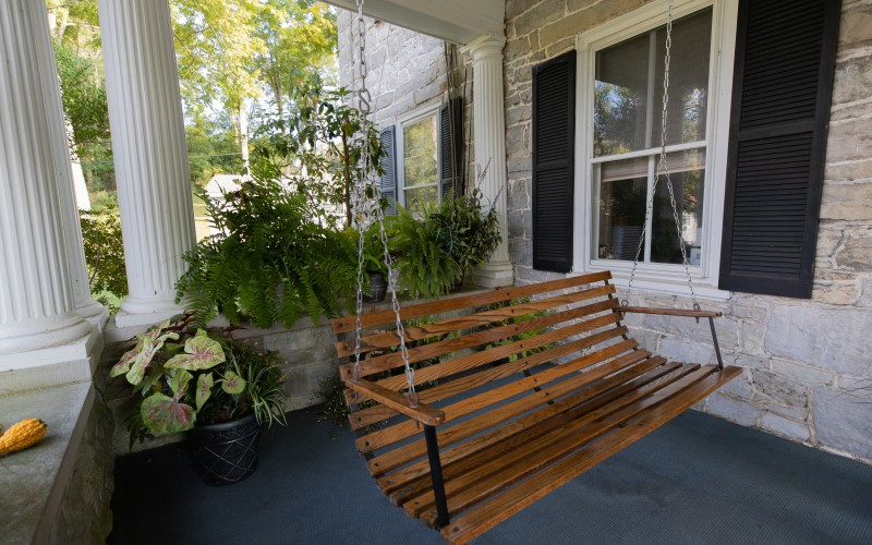 A wooden swing bench on a porch at Cove Forge Behavioral Health