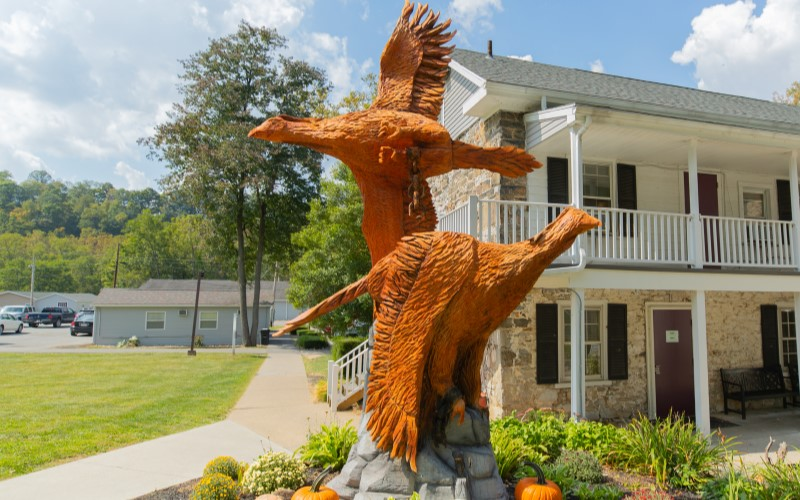 A closeup of a statue of two birds sits in a garden in front of a building at Cove Forge Behavioral Health