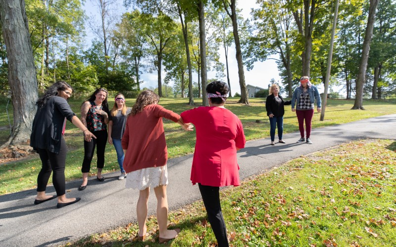 Patients and counselors participate in a blindfolded trust exercise outside at Cove Forge Behavioral Health